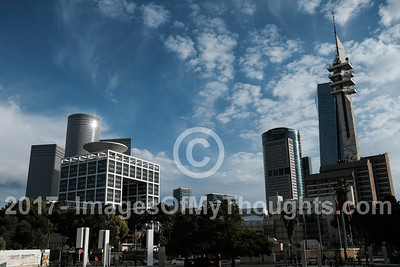 The urban skyline of Tel Aviv depicts the Azrieli towers (left) and IDF Headquarters (right).