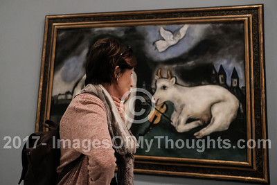 A woman studies a painting by Marc Chagall, on display in the Tel Aviv Museum of Art.