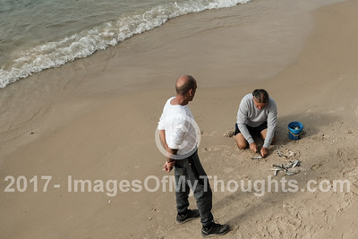 A fisherman cuts up small fish to use as bait on the Tel Aviv Mediterranean beach front.