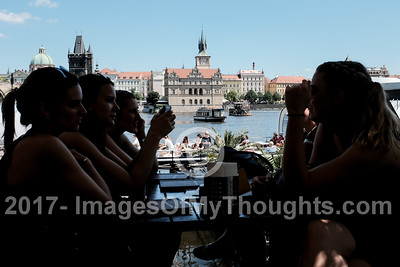 Visitors sit along the left bank (west) of the Vltava River in Mala Strana, Prague.