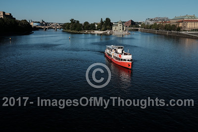 Eastward view of the Vltava River from the Stefanikuv Most Bridge depicts one of many boats offering a river cruise.
