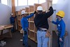 Pine Ridge Job Corps carpentry students install bookshelves in the Chadron State College Rangeland Lab conference room May 4, 2017. The shelves were made from the Nebraska Champion Colorado Spruce formerly on the Deans' Green. Students in the carpentry, painting and cement trades participated in the project. (Photo by Tena L. Cook/Chadron State College)