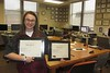 """Jordyn Hulinsky, editor of """"The Eagle"""" since 2015, poses with two of the 2017 first place award certificates the Chadron State College student newspaper earned from the Nebraska Collegiate Media Association. (Courtesy photo)"""