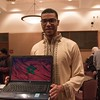 Chadron State College student Anas Haddadi poses with an image from his presentation about his home country of Morocco during Dine With Us, a lunch series sponsored by the Office of International Education. (Photo by Tena L. Cook/Chadron State College)