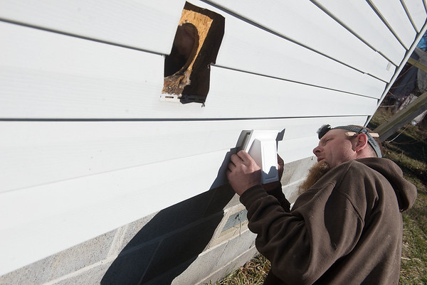 Globe/Roger Nomer David Perry installs an exaust vent for a ASHRAE fan on Wednesday at a home in Carthage.