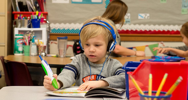 Globe/Roger Nomer Gabe Robertson uses an electronic reader during kindergarten on Thursday at Kelsey Norman Elementary.