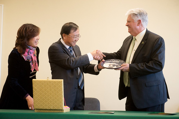 Globe/Roger Nomer Shandong Foreign Trade Vocational College President Yang Mingang and Cui Wei, director of international programs at Shandong, give Missouri Southern President Alan Marble to gift of a plate depicting Qingdao, China, on Friday at MSSU.