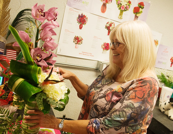 Globe/Roger Nomer<br /> Cindy Fox puts the finishing touches on a Valentine flower arrangement on Monday at Don Davis Florist.
