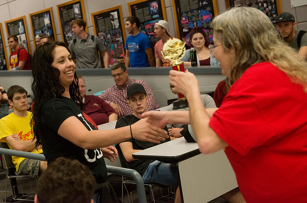 Globe/Roger Nomer<br /> Brandi Mendenall, teacher at Central High School, accepts the first place trophy for the Earth and Space Science competition on behalf of her students from Kyla Scarborough, physics faculty at Pittsburg State, during PSU's Science Day on Thursday.