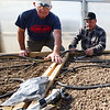 From the left: Ozark Gateway Master Gardeners Ron Wood and Dale Dintaman work to install an irrigation system inside the new greenhouse at Crosslines on Saturday afternoon.<br /> Globe | Laurie Sisk