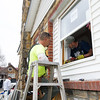 From the left: Volunteers Scott Williams and Terry Donaldson install new windows at the home of 93-year-old World War II pilot Floyd Prock on Saturday. About 10 volunteers from Habitat for Humanity, Hearts and Hammers and Compass Quest Veterans Services worked Saturday to install new windows and help with additional repairs on the home that Prock built in 1950.<br /> Globe | Laurie Sisk