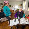 Volunteer Joyce Holcomb, center, chats with 93-year-old World War II pilot Floyd Prock inside his Joplin home on Saturday as caregiver Kathy King looks on. About 10 volunteers from Habitat for Humanity, Hearts and Hammers and Compass Quest Veterans Services worked Saturday to install new windows and help with additional repairs on the home that Prock built in 1950.<br /> Globe | Laurie Sisk