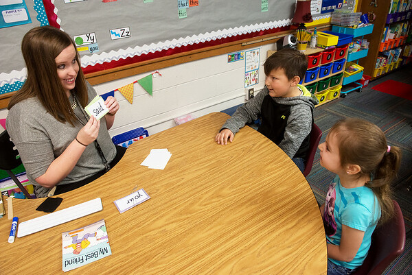 Globe/Roger Nomer Katie Hadley practices words with Xander Rainey and Caitlynn Hayden during kindergarten on Thursday at Kelsey Norman Elementary.