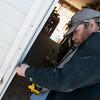 Globe/Roger Nomer<br /> Joe McManus works on weather stripping on Wednesday at a house in Carthage.
