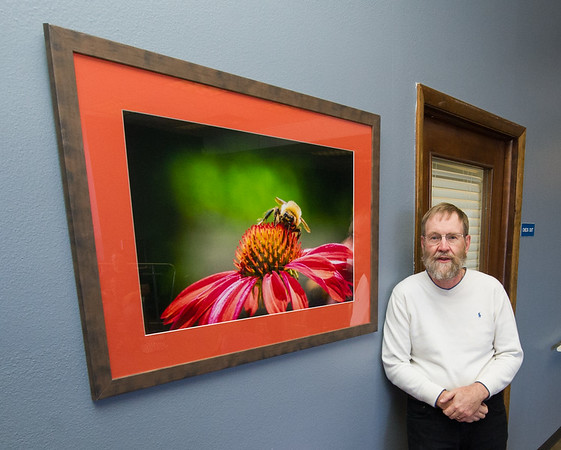 Dr. Howard Thmpson stands beside one of several photographs he created that grace the walls of the newly remodeled Community Clinic on Wednesday. In addition to donating the prints, Thompson also volunteers at the cinic each Wednesday.<br /> Globe | Laurie Sisk
