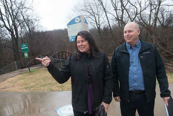 Globe/Roger Nomer Elizabeth Bowen and Tim Conklin talk about the Razorback Greenway Trail in Bentonville on Tuesday.