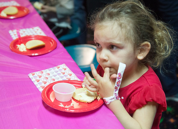 Globe/Roger Nomer Paislee Jones, 2, Webb City, samples her cookie creation during an early Valentine's Day event at Roller City Skate and Play of Joplin on Thursday.