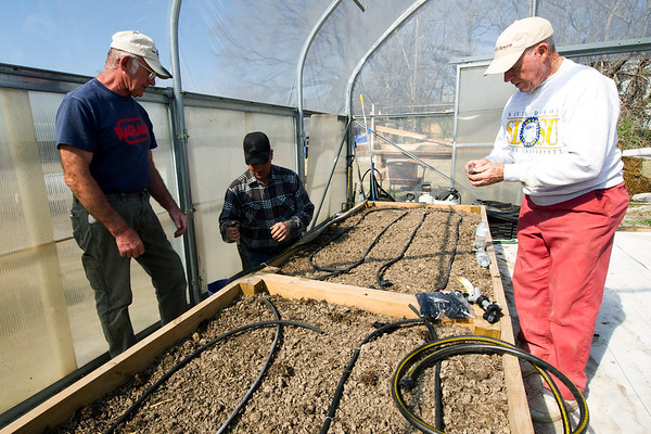 From the left: Ozark Gateway Master Gardeners Ron Wood, Dale Dintaman and Arthur Dahms work to install an irrigation system inside the new greenhouse at Crosslines on Saturday afternoon.<br /> Globe | Laurie Sisk