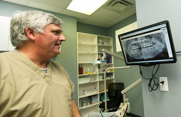 Dr. Ed McAllister examines a dental xray on Wednesday at the Community Clinic.<br /> Globe | Laurie Sisk