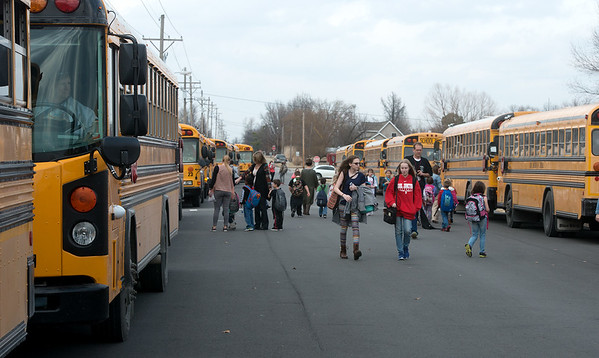 Globe/Roger Nomer Carl Junction students board busses on Monday afternoon.