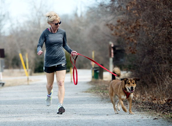 Globe/Roger Nomer Kelly Johnson runs with Ashlee on Tuesday on the Frisco Trail.