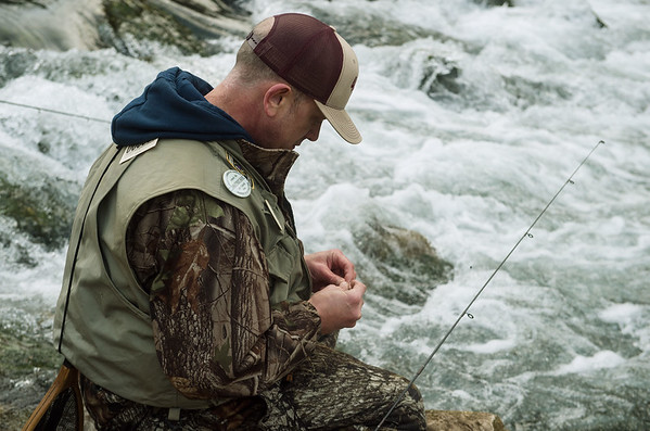 Ryan Cleveland, Kansas City, Mo., baits his line while fishing on opening day at Roaring River State Park on Sunday.<br /> Globe | Roger Nomer