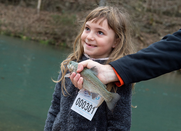 Seven-year old Isabella Jones, Monett, poses for a photo she helped reel in on Sunday at Roaring River State Park. Jones wanted a photo with the fish, but wasn't thrilled about touching it.<br /> Globe | Roger Nomer