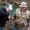 Dave Houlihan, Carthage, helps Calee Haslip with a fish she caught during opening day at Roaring River State Park on Sunday.<br /> Globe | Roger Nomer