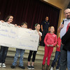 Globe/Roger Nomer<br /> Stapleton Elementary students and Wes Brownfield present Lourdes Hasty with a check for money raised from an art auction for her recovery expenses.  Hasty returned to work at the school on Monday morning.