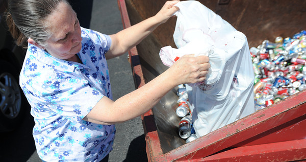 Globe/T. Rob Brown<br /> Cindy Epler, of Hallowell, dumps a bag of aluminum cans into the recycle bins at the Joplin Recycling Center Friday morning, April 5, 2013.