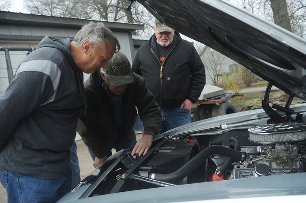Globe/Roger Nomer<br /> Bill Smith looks under the hood of his restored '68 Camaro with Mike Sand, center, and John Newbery on Wednesday morning.