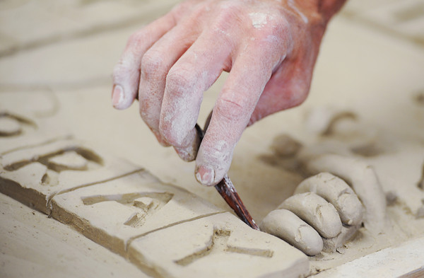 """Globe/T. Rob Brown<br /> The hands of Justin Hale, of Joplin, create clay fingers for """"The Rise of the Phoenix,"""" a sculptured clay tile mural Saturday afternoon, April 20, 2013, at Phoenix Fired Art Community Clay Center, 1603 S. Main St., Joplin. The center raised the needed funds via Kickstarter, a crowdscource funding website."""
