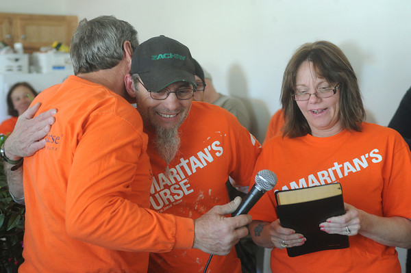 Globe/Roger Nomer<br /> (from left) Dan Helmich, construction supervisor for Samaritan's Purse, hugs Tommy Harper as he and his wife Darlene receive a Bible to commemorate their new home on Friday.  After losing their house in the May 22, 2011, tornado, Samaritan's Purse built the Harpers a new house on Empire.