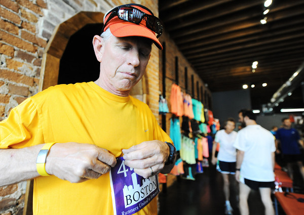Globe/T. Rob Brown<br /> Greg Edster, of Joplin, puts on a Boston bib, made by Rufus Racing, at The Run Around Running Co., just before 144 seconds of silence in downtown Joplin Wednesday evening, April, 17, 2013. The event's intent was to support those injured in the Boston bombing.