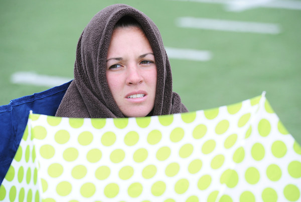Globe/T. Rob Brown<br /> Daysha Harak, of Oklahoma, tries to keep warm with a blanket and keeps her umbrella at the ready during Saturday afternoon's Bill Williams/Bob Laptad Invite at Missouri Southern State University's Fred G. Hughes Field.