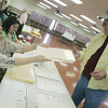 Globe/Roger Nomer<br /> Marie Nepple hands a ballot to Joe Hawkins at the Baxter Springs Community Center on Tuesday.