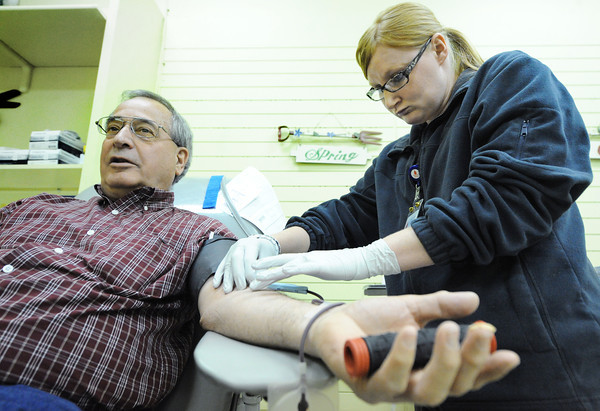 Globe/T. Rob Brown<br /> Jim Vannaman of Diamond gives blood with assistance from Jennie Poole, donor staff with Community Blood Center of the Ozarks, Wednesday morning, April 3, 2013, at Joplin's Northpark Mall.