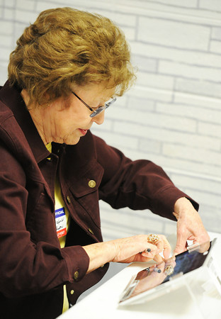 Globe/T. Rob Brown<br /> Webb City supervisory election judge Maxine Carlson slides a voter's registration card through a reader on an electronic tablet Tuesday afternoon, April 2, 2013, at Webb City Junior High School. The tablet is connected to the voter registration database.