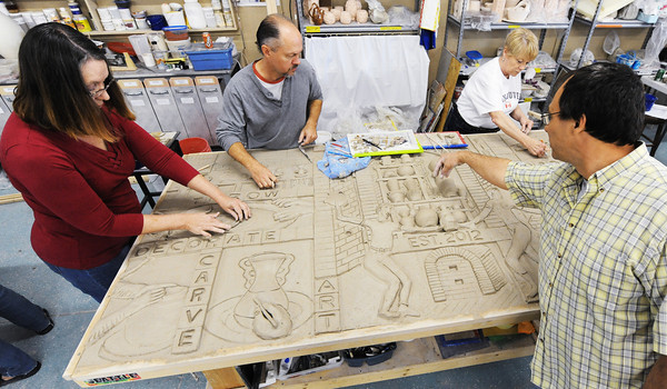 """Globe/T. Rob Brown<br /> Lead designer of """"The Rise of the Phoenix"""" mural, Trent Tally (below right) of rural Fayetteville, Ark., speaks with artists (from left) Linda Whitteck, of Webb City, Tom Jones, of Carthage, and Vicki Mays, of Carl Junction, as they work on the sculptured clay tile mural Saturday afternoon, April 20, 2013, at Phoenix Fired Art Community Clay Center, 1603 S. Main St., Joplin. The center raised the needed funds via Kickstarter, a crowdscource funding website."""