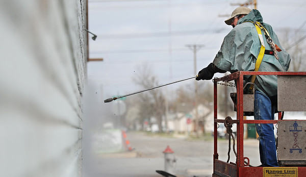 Globe/T. Rob Brown<br /> Doug Whitehead, of Joplin, a finishing painter with Spellman & Associates, uses a pressure washer to clean the bricks of a building on the southeast corner of South Main Street and West 16th Street Monday morning, April 1, 2013. Whitehead said he was getting ready to paint the brick building.