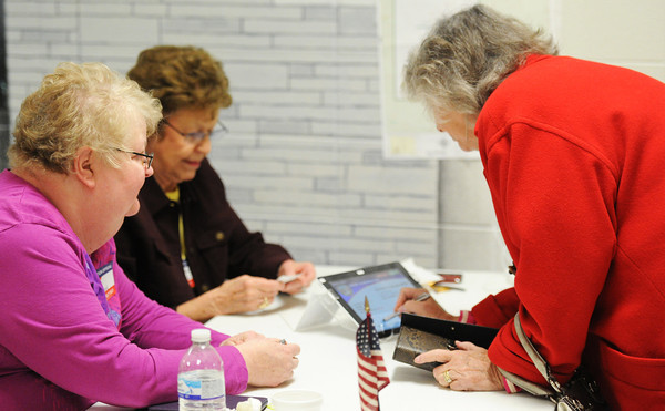 """Globe/T. Rob Brown<br /> Cathy Dilworth of Webb City signs an electronic tablet for voter registration Tuesday afternoon, April 2, 2013, at Webb City Junior High School. Supervisory election judges Connie Houston, left, and Maxine Carlson assist her. """"Back when we were at 30-some voters (in the precinct), I set our goal at 100,"""" Carlson said. """"We've got 64 now so we might get 150. We usually get between 150 and 200 to show up for school board elections."""""""