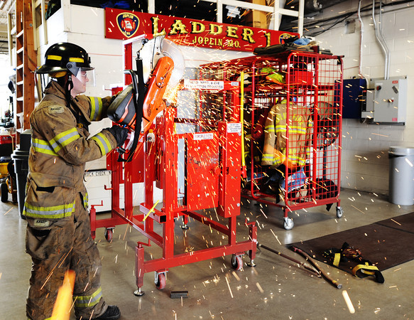 Globe/T. Rob Brown<br /> Freddie Friedman, a Joplin firefighter-paramedic, practices using an emergency saw Wednesday afternoon, April 3, 2013, at the Joplin Fire Department, Station No. 1, in downtown Joplin.