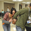 Globe/Roger Nomer<br /> Debbi Hindon, portraying a police officer, places Steven Lane, Ottawa, under arrest during a poverty simulation at Tuesday's homeless summit at Pittsburg's Memorial Auditorium.