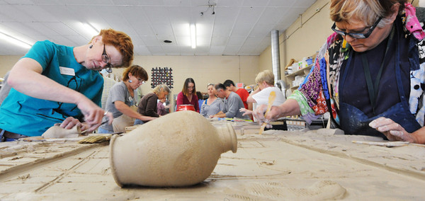"""Globe/T. Rob Brown<br /> """"The Rise of the Phoenix,"""" a sculptured clay tile mural Saturday afternoon, April 20, 2013, gets worked on at Phoenix Fired Art Community Clay Center, 1603 S. Main St., Joplin. The center raised the needed funds via Kickstarter, a crowdscource funding website. Artists, including Heather Grills (left), owner and executive director, and Jacque Moody-McDonald (right), of Sarcoxie."""
