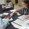 Globe/Roger Nomer<br /> DeAnna Goering, portraying a social services caseworker, helps out Aaron Lovelady, Wichita, at Tuesday's poverty simulation during the homeless summit at Pittsburg's Memorial Auditorium.