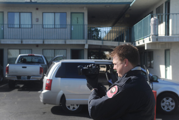 Globe/Roger Nomer<br /> An investigater examines the scene of a morning shooting at Motel 6 in Joplin on Friday.