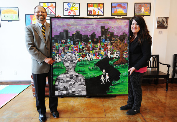 """Globe/T. Rob Brown<br /> Michael Beatty, publisher of The Joplin Globe, holds an acrylic on canvas painting titled """"Joplin-New Beginnings"""" created by Pittsburg, Kan., artist Elizabeth Cosby."""