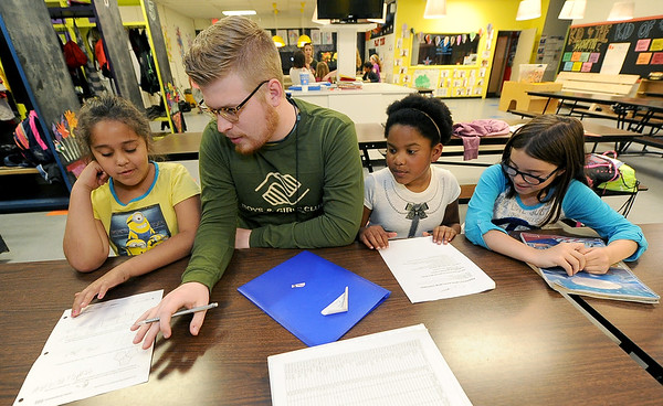 Boys and Girls Club tutor Jake Messer helps kids with their homework on Thursday at the club. From the left: Keana Caton, 9, Adyson Ratliff, 8 and Adalynn Osborn, 9.<br /> Globe | Laurie Sisk