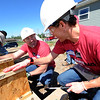 From the left: Owens Corning volunteers Bart Stanphill, left, of Toledo, Ohio and Trinke Vaughan, of Atlanta, Ga., help construct subflooring for a Habitat for Humanity House at 2415 S. Porter on Thursday. Vaughan will be transferring from Atlanta to Joplin in July.<br /> Globe | Laurie Sisk