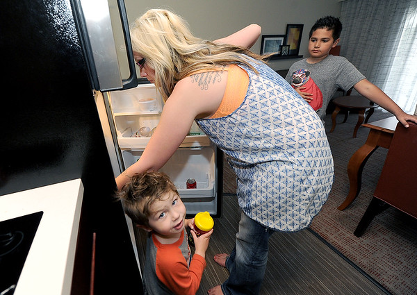 Bree O'Haro searches the refrigerator for refreshments for her two sons, Dominick Sansalone, 9 and Draven Showalter, 2. The family was displaced from their Joplin home after sewage problems.<br /> Globe | Laurie Sisk